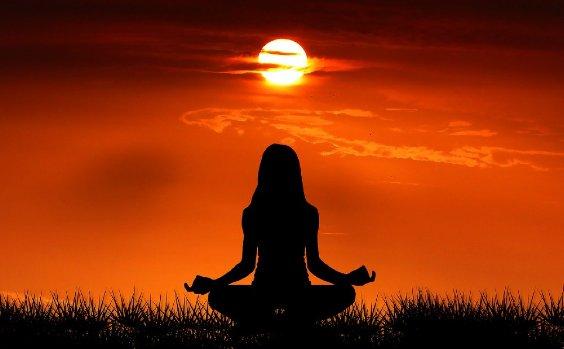 Frau macht Yoga bei Sonnenuntergang